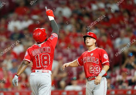 Los Angeles Angels' Brian Goodwin (18) crosses the plate with a two-run home run off Cincinnati Reds relief pitcher David Hernandez, as Matt Thaiss (23) waits with congratulations during the ninth inning of a baseball game, in Cincinnati