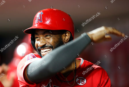 Los Angeles Angels' Brian Goodwin smiles as he is congratulated in the dugout following a two-run home run off Cincinnati Reds relief pitcher David Hernandez during the ninth inning of a baseball game, in Cincinnati