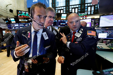 Stock Photo of Gregory Rowe, Daniel Kryger, Mario Picone. Traders Gregory Rowe, left, and Daniel Kryger, center, work with specialist Mario Picone on the floor of the New York Stock Exchange, . Stock markets turned higher on Tuesday as China stabilized its currency after allowing it to depreciate against the dollar in response to President Donald Trump's decision to put more tariffs on Chinese goods