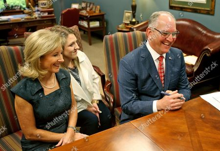 With his wife Donna, left, and daughter Sarah Ellen by his side, Louisiana Governor John Bel Edwards signs paperwork at the Louisiana Secretary of State's office to sign up to run in the upcoming election, in Baton Rouge, La., . The candidate sign-up period for Louisiana's statewide elections ends Thursday, with the governor's race at the top of the ballot