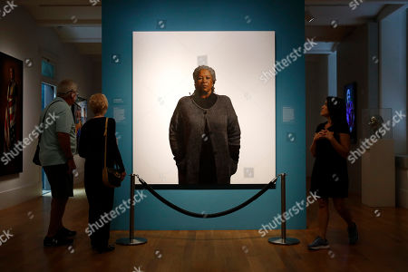 Visitors view a portrait of Nobel laureate Toni Morrison, painted by the artist Robert McCurdy, at the National Portrait Gallery in Washington. Morrison, a pioneer and reigning giant of modern literature, died Monday at age 88
