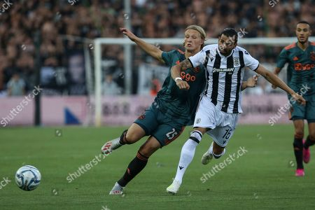 José Ángel Crespo, Kasper Dolberg. PAOK's José Ángel Crespo, right, challenges for the ball with Ajax's Kasper Dolberg during the Champions League third qualifying round, first leg soccer match between PAOK FC and AFC Ajax, at Toumba Stadium in the northern Greek port city of Thessaloniki