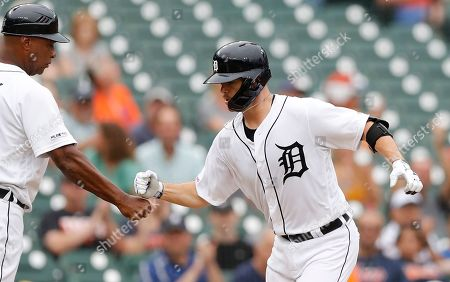 Detroit Tigers' Jake Rogers is congratulated by third base coach Dave Clark after a solo home run during the fifth inning of the first game of a baseball doubleheader against the Chicago White Sox, in Detroit