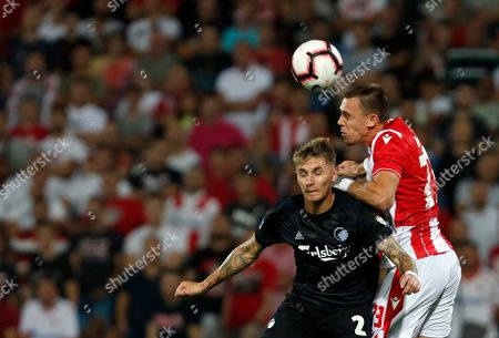 Red Star's Milan Rodic, right, jumps for the ball with Copenhagen's Guillermo Varela during the Champions League third qualifying round, first leg soccer match between Red Star and FC Copenhagen on the stadium Rajko Mitic in Belgrade, Serbia