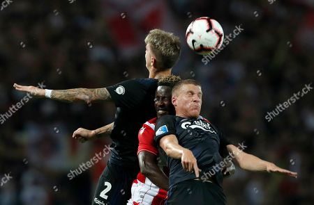 Red Star's Richmond Boakye, center, jumps for the ball with Copenhagen's Guillermo Varela, left, and Copenhagen's Pep Biel Mas Jaume during the Champions League third qualifying round, first leg soccer match between Red Star and FC Copenhagen on the stadium Rajko Mitic in Belgrade, Serbia