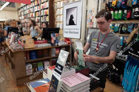 """Spencer Robelen, visual merchandiser for the Strand Bookstore, arranges a display of Toni Morrison books, in New York. Nobel laureate Morrison, a pioneer and reigning giant of modern literature whose imaginative power in """"Beloved,"""" ''Song of Solomon"""" and other works transformed American letters by dramatizing the pursuit of freedom within the boundaries of race, has died at age 88"""