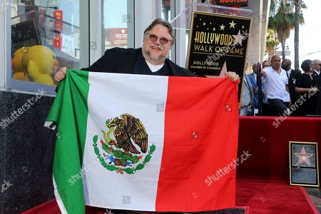 Guillermo del Toro poses with the Mexican flag following a ceremony honoring him with a star at the Hollywood Walk of Fame, in Los Angeles