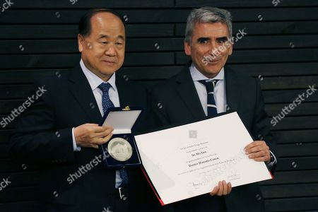 Chinese author and Literature Nobel laureate 2012 Mo Yan (L) is named Honoris Causa Doctor by Carlos Pena (R), dean of the Diego Portales Universiy, after the master class 'My literary resources: The rivers and literature', in Santiago, Chile, 06 August 2019.