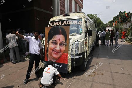 A worker decorates a vehicle that will carry the the body of former Indian Foreign Minister Sushma Swaraj for final rites as a person takes selfie with Swaraj's life size portrait at the Bharatiya Janata Party headquarters in New Delhi, India, . Swaraj, a leader of the ruling Hindu nationalist Bharatiya Janata Party died at a hospital Tuesday. She was 67