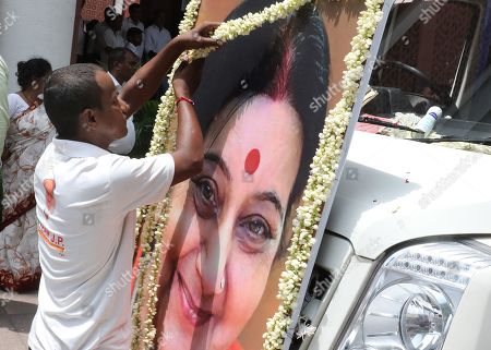 Indian man hands flowers on the picture of former Indian External Affairs Minister and top Bharatiya Janata Party (BJP) leader Sushma Swaraj at the BJP headquarters in New Delhi, India, 07 August 2019. The 67-year-old Sushma Swaraj died on 06 August after suffering a massive heart attack. Her last rites will be performed in New Delhi.