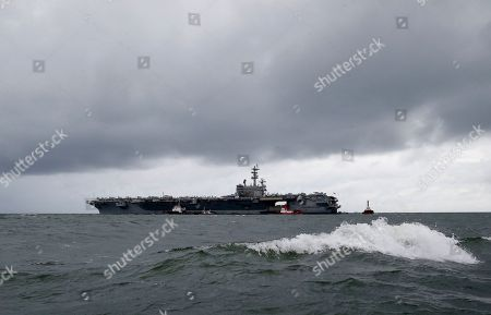 Rain clouds loom over the U.S. aircraft carrier USS Ronald Reagan as it is anchored off Manila Bay, Philippines, for a port call . The USS Ronald Reagan is cruising in international waters in the South China Sea amid tensions in the disputed islands, shoals and reefs between China and other claimant-countries as Philippines, Vietnam and Malaysia