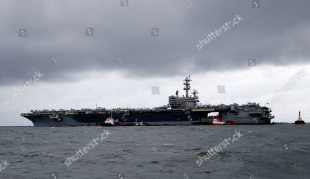 Rain clouds loom over the U.S. aircraft carrier USS Ronald Reagan as it is anchored off Manila Bay, Philippines for a port call . The USS Ronald Reagan is cruising in international waters in the South China Sea amid tensions in the disputed islands, shoals and reefs between China and other claimant-countries as Philippines, Vietnam and Malaysia