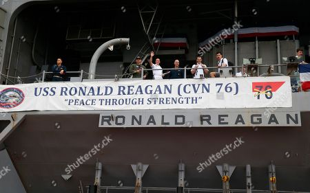 U.S. Navy personnel and crew aboard the U.S. aircraft carrier USS Ronald Reagan wave to the departing media as it is anchored off Manila Bay, Philippines, for a port call . The USS Ronald Reagan is cruising in international waters in the South China Sea amid tensions in the disputed islands, shoals and reefs between China and other claimant-countries as Philippines, Vietnam and Malaysia
