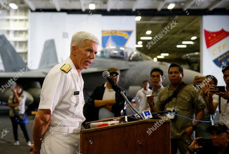 U.S. Rear Adm. Karl Thomas, commander of the Battle Force 7th Fleet, addresses the media aboard the U.S. aircraft carrier USS Ronald Reagan as it is anchored off Manila Bay, Philippines, . The USS Ronald Reagan is cruising in international waters in the South China Sea amid tensions in the disputed islands, shoals and reefs between China and other claimant-countries as Philippines, Vietnam and Malaysia
