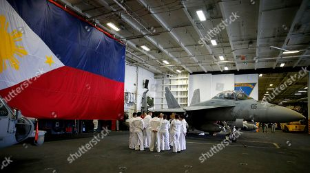 Amidst a giant backdrop of a Philippine flag and a fighter jet, Filipino-American crewmen of the U.S. aircraft carrier USS Ronald Reagan huddle following an interview off Manila Bay, Philippines. The USS Ronald Reagan is cruising in international waters in the South China Sea amid tensions in the disputed islands, shoals and reefs between China and other claimant-countries as Philippines, Vietnam and Malaysia