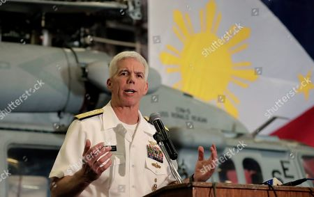 With the Philippine flag in the background, Rear Adm. Karl Thomas, commander of the Battle Force 7th Fleet, addresses the media aboard the aircraft carrier USS Ronald Reagan as it is anchored off Manila Bay, Philippines, . The USS Ronald Reagan is cruising in international waters in the South China Sea amid tensions in the disputed islands, shoals and reefs between China and other claimant-countries as Philippines, Vietnam and Malaysia