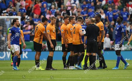 Wolverhampton Wanderers players surround referee Andre Marriner and his assistants at full time