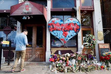 A pedestrian passes a makeshift memorial for the slain and injured victims of a mass shooting that occurred in the Oregon District early Sunday morning, in Dayton, Ohio. President Donald Trump headed to Dayton and El Paso, Texas on Wednesday to offer a message of healing and unity, but he will be met by unusual hostility in both places by people who fault his own incendiary words as a contributing cause to the mass shootings