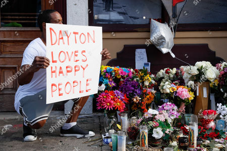 Damon Smith presents what he describes as a positive message before the arrival of President Donald Trump near a makeshift memorial for the slain and injured victims of a mass shooting that occurred in the Oregon District early Sunday morning, in Dayton, Ohio. President Donald Trump headed to Dayton and El Paso, Texas on Wednesday to offer a message of healing and unity, but he will be met by unusual hostility in both places by people who fault his own incendiary words as a contributing cause to the mass shootings