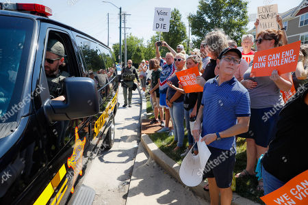 Stock Picture of Demonstrators gather while authorities keep them across the street during their protest against the arrival of President Donald Trump outside Miami Valley Hospital after a mass shooting that occurred in the Oregon District early Sunday morning, in Dayton, Ohio. Trump headed to Dayton and El Paso, Texas on Wednesday to offer a message of healing and unity, but he will be met by unusual hostility in both places by people who fault his own incendiary words as a contributing cause to the mass shootings