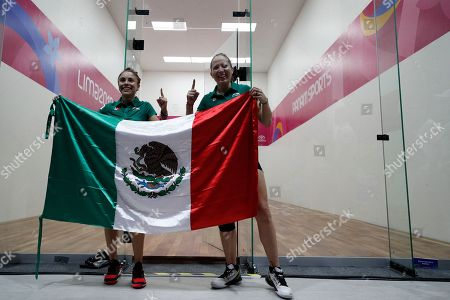 Mexico's Paola Longoria, left, and Samantha Salas, pose for pictures with a Mexican national flag as they celebrate defeating Guatemala's Gabriela Martinez and Maria Rodriguez in the women's racquetball team gold medal match at the Pan American Games in Lima, Peru