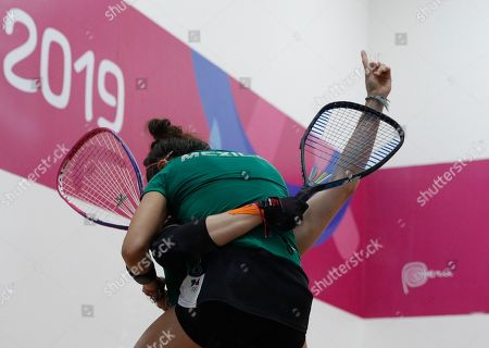 Mexico's Samantha Salas holds up both her teammate Paola Longoria and a finger representing number one after they defeated Guatemala's Gabriela Martinez and Maria Rodriguez in the women's racquetball team gold medal match at the Pan American Games in Lima, Peru