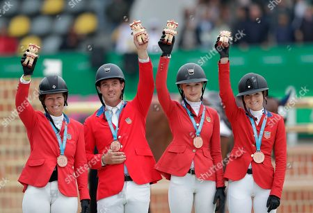 Stock Photo of Bronze medalists Elizabeth Madden, from left, Alex Granato, Eve Jobs and Lucy Deslauriers of the United States, pose for a photo holding up their souvenir mascot during the medal ceremony for the equestrian jumping team, at the Pan American Games in Lima, Peru