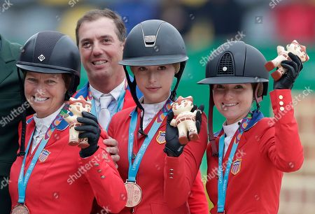 Stock Picture of Bronze medalists Elizabeth Madden, from left, Alex Granato, Eve Jobs and Lucy Deslauriers of the United States, pose for a photo holding up their souvenir mascot during the medal ceremony for the equestrian jumping team, at the Pan American Games in Lima, Peru