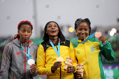 Gold medalist Elaine Thompson of Jamaica, center, silver medalist Michelle-Lee Ahye of Trinidad and Tobago, left, and bronze Vitoria Cristina Silva of Brazil pose for photos at the podium for the women's 100m during the athletics at the Pan American Games in Lima, Peru