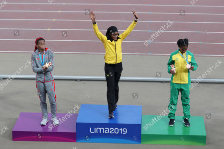 Gold medalist Elaine Thompson of Jamaica waves flanked by silver medalist Michelle-Lee Ahye of Trinidad and Tobago, left, and bronze medalist Vitoria Cristina Silva of Brazil at the podium for the women's 100m during the athletics at the Pan American Games in Lima, Peru