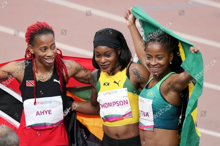 The gold medalist Elaine Thompson of Jamaica, center, silver medalist Michelle-Lee Ahye of Trinidad and Tobago, left, and bronze medalist Vitoria Cristina Silva of Brazil celebrate after the women's 100m final during the athletics at the Pan American Games in Lima, Peru