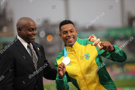 Nine-time Olympic gold medalist Carl Lewis looks at silver medalist Paulo Camilo De Oliveira of Brazil showing his silver medal on the podium for the men's 100m during the athletics at the Pan American Games in Lima, Peru