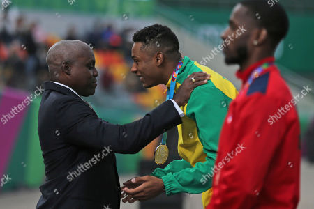 Paulo Andre of Brazil, center, receives his silver medal from nine-time Olympic gold medalist Carl Lewis at the podium for the men's 100m during the athletics final at the Pan American Games in Lima, Peru