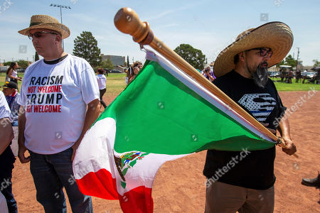Fernando Montoya, right, waves a Mexican flag to protest the visit of President Donald Trump to the border city after the Aug. 3 mass shooting in El Paso, Texas, . Trump headed to El Paso, after visiting Dayton, Ohio on Wednesday to offer a message of healing and unity, but he will be met by unusual hostility in both places by people who fault his own incendiary words as a contributing cause to the mass shootings