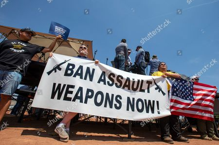 Demonstrators hold a banner to protest the visit of President Donald Trump to the border city after the Aug. 3 mass shooting in El Paso, Texas, . Trump headed to El Paso, after visiting Dayton, Ohio on Wednesday to offer a message of healing and unity, but he will be met by unusual hostility in both places by people who fault his own incendiary words as a contributing cause to the mass shootings