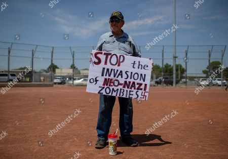 Gilberto Zuniga holds a sign to protest the visit of President Donald Trump to the border city after the Aug. 3 mass shooting in El Paso, Texas, . Trump headed to El Paso, after visiting Dayton, Ohio on Wednesday to offer a message of healing and unity, but he will be met by unusual hostility in both places by people who fault his own incendiary words as a contributing cause to the mass shootings