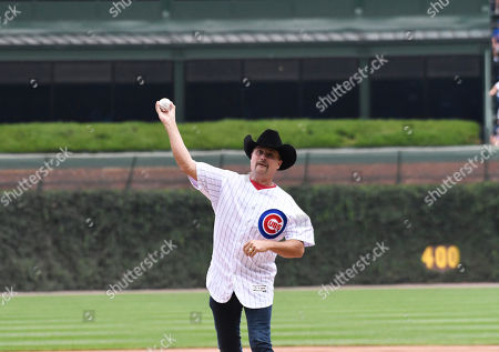 Stock Image of Country Music artist John Rich throws out a ceremonial first pitch before a baseball game between the Chicago Cubs and the Oakland Athletics, in Chicago