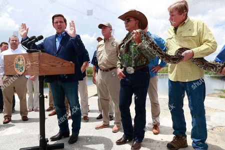 Ron DeSantis, Ron Bergeron, Joe Wasilewski. Florida Gov. Ron DeSantis, left, speaks during a news conference, as Ron Bergeron, second from right, South Florida Water Management District Governing Board member, and conservation biologist Joe Wasilewski, right, hold a 12-ft. python at Everglades Holiday Park, in Fort Lauderdale, Fla. DeSantis said the state is expanding its efforts to eradicate invasive pythons in the Everglades and is working with the federal government to get snake hunters to remote areas of Big Cypress National Preserve