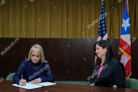Justice Secretary Wanda Vazquez signs a document after she was sworn in as governor of Puerto Rico by Supreme Court Justice Maite Oronoz, right, in San Juan, Puerto Rico, in San Juan Puerto Rico. Vazquez took the oath of office early Wednesday evening at the Puerto Rican Supreme Court, which earlier in the day ruled that Pedro Pierluisi's swearing in last week was unconstitutional. Vazquez was joined by her daughter Beatriz Diaz Vazquez and her husband Judge Jorge Diaz