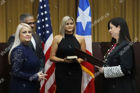 Wanda Vazquez Garced (L), swears in the position of governor before the Chief Justice of the Supreme Court, Maite Oronoz (R), accompanied by her husband, Judge Jorge Diaz Reveron (2-L) and her daughter Beatriz Diaz (C), in San Juan, Puerto Rico, 07 August 2019. Vazquez became the new Governor of the island, as provided by the legal system, after the Supreme Court annulled the controversial swearing of Pedro Pierluisi.