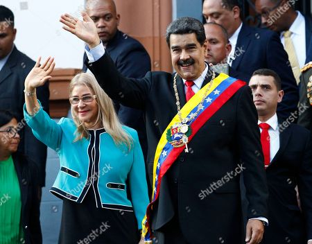 Nicolas Maduro, Cilia Flores. Venezuela's President Nicolas Maduro, center, and his first lady Cilia Flores, wave to supporters as they leave the National Pantheon after attending a ceremony to commemorate an 1800's independence battle, in Caracas, Venezuela, . Sweeping new U.S. sanctions freeze all of the Maduro government's assets in the U.S. and even threaten to punish companies from third countries that keep doing business with his socialist administration