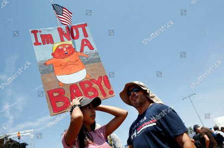 Stock Photo of Demonstrators hold a sign to protest the visit of President Donald Trump to the border city following Saturday's mass shooting in El Paso, Texas, . Trump headed to El Paso, after visiting Dayton, Ohio on Wednesday to offer a message of healing and unity, but was met by unusual hostility in both places by people who fault his own incendiary words as a contributing cause to the mass shootings