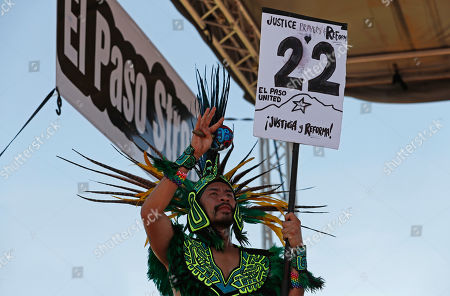 A dancer with the group Danza Azteca holds a sign with the number of victims who died in Saturday's mass shooting during a protest against the visit of President Donald Trump to the border city of El Paso, Texas, . Trump headed to El Paso, after visiting Dayton, Ohio on Wednesday to offer a message of healing and unity, but was met by unusual hostility in both places by people who fault his own incendiary words as a contributing cause to the mass shootings
