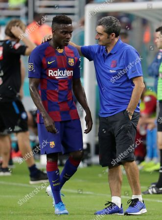Ernesto Valverde, Moussa Wague. Barcelona's Moussa Wague, left, talks with coach Ernesto Valverde during the first half against Napoli in a soccer match, in Miami Gardens, Fla. Barcelona won 2-1