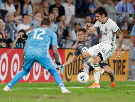 Stock Photo of Portland Timbers defender Zarek Valentin (16) and goalkeeper Steve Clark defend against a shot by Minnesota United midfielder Ethan Finlay, center, during the second half of a U.S. Open Cup soccer semifinal, in St. Paul, Minn