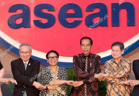 From left to right, Thai Foreign Minister Don Pramudwinai, his Indonesian counterpart Retno Marsudi, Indonesian President Joko Widodo and Secretary General of Association of Southeast Asian Nations (ASEAN) Lim Jock Hoi hold hands with other delegates as they pose for photographers during the inauguration ceremony of the new ASEAN Secretariat in Jakarta, Indonesia