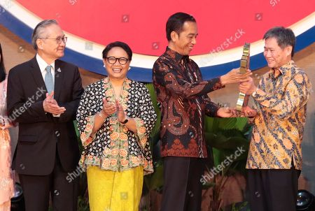 Indonesian President Joko Widodo, second right, hands a symbolic key to the Secretary General of Association of Southeast Asian Nations (ASEAN) Lim Jock Hoi, right, as Thai Foreign Minister Don Pramudwinai, left, and his Indonesian counterpart Retno Marsudi applaud during the inauguration ceremony of the new ASEAN Secretariat in Jakarta, Indonesia