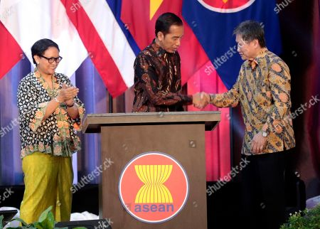 Indonesian President Joko Widodo, center, shakes hands with the Secretary General of Association of Southeast Asian Nations (ASEAN) Lim Jock Hoi as Indonesian counterpart Retno Marsudi applaud during the inauguration ceremony of the new ASEAN Secretariat in Jakarta, Indonesia