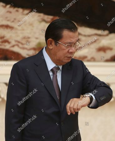 Cambodian Prime Minister Hun Sen looks at his watch while waiting for Sri Lankan President Maithripala Sirisena for a meeting at Peace Palace in Phnom Penh, Cambodia, . Sirisena is on a four-day state visit to strengthen a bond of friendship between the two Asian nations