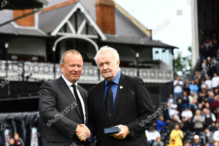 Stock Image of Former player Rodney Marsh is presented with an award at half time by Director David Daly